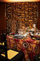 Rohatyn Room dining table adorned with tropical floral centerpiece and African fabric