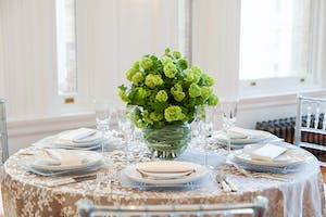 Taupe floral patterned tabletop with bell glassware, white china, and green floral centerpiece