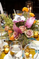 Centerpiece with orange and pink roses and tropical flowers surrounded by votive candles