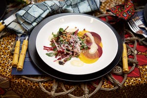 Rainbow beet carpaccio and mixed greens with toasted pecans and parmesean on a white coupe plate