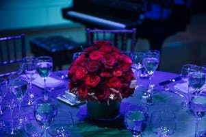 Centerpiece of red roses on a dinner table washed in blue light in the Weill Music Room