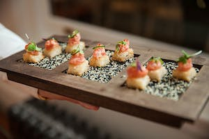 Tray lined with black and white sesame seeds holding hors d'oeuvres of tuna tartare on crispy rice