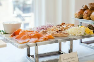 Marble platter of smoked salmon, chopped onion, capers, chopped egg, and chive cream cheese