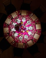 Round formal table setting as seen from above, with fuchsia table linen and floral centerpiece