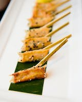 Pot sticker hors d'oeuvres with bamboo toothpicks on a banana-leaf lined white tray