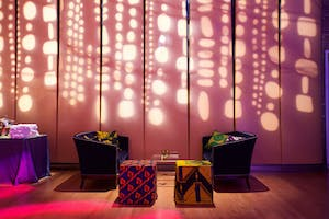 Blue armchairs and patterened ottomans in front of a wall with gobo lighting projections