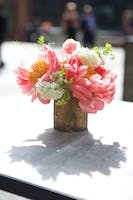 Sunlit floral centerpiece of coral peonies, white hydrangeas, and greenery on the Weill Terrace