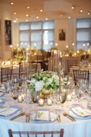 Weill Terrace Room dining tables with candles and low green and white floral centerpieces