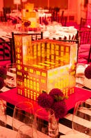 Gold dining table centerpiece in the shape of Carnegie Hall glowing from within