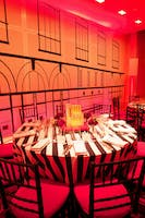 Black and white striped gala dinner table next to a wall outlined to match Carnegie Hall's façade
