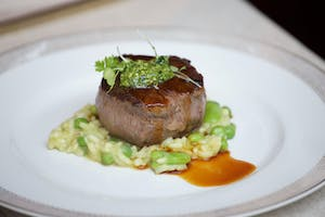 Filet mignon on spring pea risotto topped with lemon chimichurri sauce