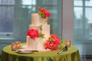 Three-tier white wedding cake decorated with large coral peonies set on a sage green tabletop