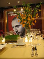 Maize tabletop with alternating centerpieces of green grass and yellow orchids in the Rohatyn Room