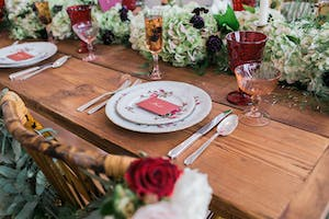 Floral china and red-tinted glassware on a rustic table with red, white, and green floral accents