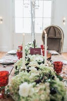 White and green floral runner on a formal dining table with red glassware and white candles