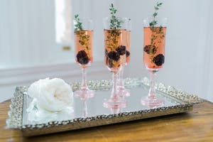 Pink flutes of champagne garnished with blackberries and herbs on an ornate silver tray