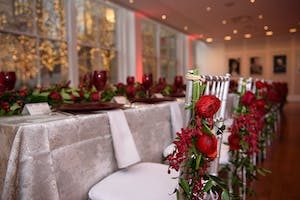 Silver dining chair at a King's table adorned with red ranunculus, red orchids, and greenery