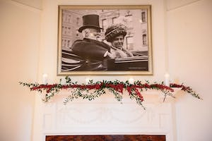 Florals adorning a mantel below a portrait of Andrew Carnegie and Louise Whitfield in the May Room