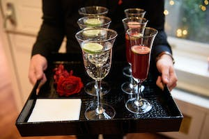 Glasses of sparkling water with lime and flutes of red champagne cocktail on a black square tray