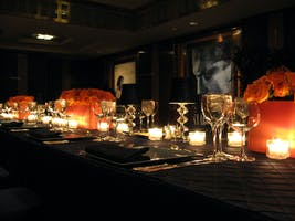 Intimate Rohatyn Room dining table dressed with navy linen, orange roses, and crystal cabaret lamps