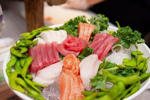 Colorful sashimi platter rimmed with pods of edamame
