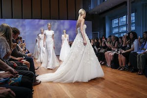 Models walk the center runway in a bridal fashion show in the Weill Music Room