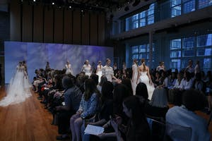 Models walk multiple runway aisles in a bridal fashion show finale in the Weill Music Room