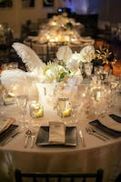 Modern dinner table and centerpiece of white orchids, proteas, roses, anthurium, and feather plumes