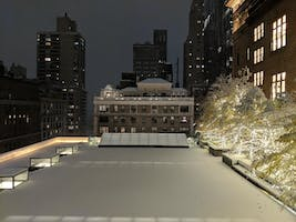 Expanse of the Weill Terrace covered in snow at night, trees lit with white winter lights