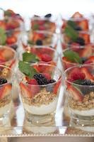 Individual fresh berry, yogurt, and granola parfaits with mint garnish set on a silver tray