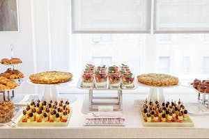 Breakfast station set with fruit and yogurt parfaits, quiche, fresh fruit skewers, and pastries
