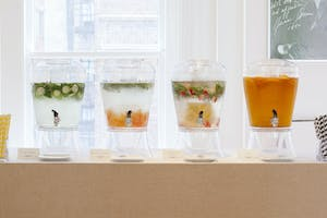 Colorful chilled fresh fruit-infused waters and juices displayed in glass dispensers