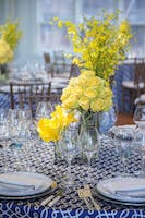 Blue scroll tabletop and yellow rose, calla lily, and orchid centerpiece in the Weill Terrace Room