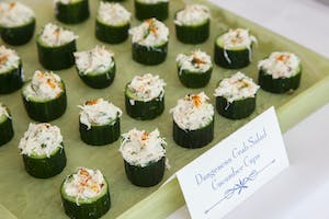 Neat rows of Dungeness crab salad cucumber cup hors d'oeuvres on a tray