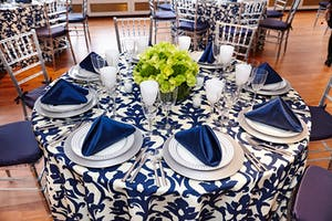 Blue and white damask patterned tabletop with blue napkins and bright green floral centerpiece
