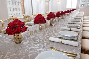 May Room dining table with damask linen, bell glassware, gold flatware, and red rose centerpieces