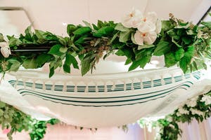 Under a chuppah adorned with white orchids and greenery