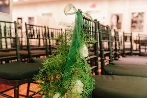 Black wedding ceremony chair adorned with green ribbon, evergreen branches, and white roses