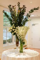 Escort card display with tall arrangements of greenery, white roses, and white delphinium