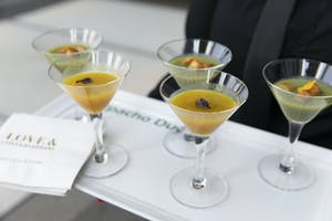 Duo of yellow and green gazpacho with floral garnish in martini glasses on a white serving tray
