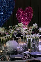 Modern dining tables with abundant white calla lilies against a background of heart sculptures