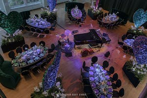 Lushly set dining tables in the Weill Music Room surrounding a jazz band setup with grand piano