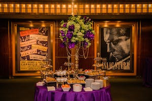Rohatyn Room dessert station with a tall centerpiece of purple orchids and green hydrangeas