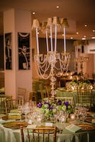 Gala dinner tables with apple green linens, gold chairs, purple florals, and crystal candelabra