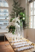 Escort cards displayed on wood table with tall arrangements of white orchids and lilies