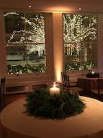 Winter reception décor in the Weill Terrace Room, a snowy terrace and holiday lights as a backdrop