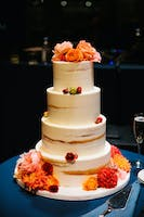 Four-tier wedding cake adorned with peonies, dahlias, and ranunculus in peach, orange, and red