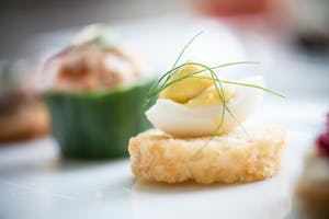 Deviled quail egg on mini toast hors d'oeuvre with dill garnish by Constellation Culinary Group