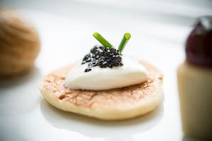 Bite-sized black caviar and crème fraîche blini with chive garnish by Constellation Culinary Group