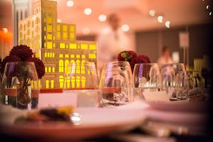Sparkling stemless glassware, clusters of red zinnias, and glowing gold Carnegie Hall centerpiece